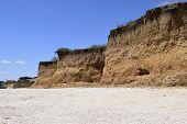 Precipice Coast Near The Sea. The Clay Cliff On The Seashore. Visiting Stunning Sandy Beach. Blue Sk poster