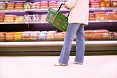 picture of grocery store  - woman buying in the grocery store and holding shopping basket - JPG