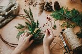 Making Rustic Christmas Wreath. Hands Holding Berries, Fir Branches, Pine Cones, Thread, Scissors On poster