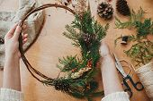Hands Holding Rustic Christmas Wreath With Pine Cones, Berries, Fir Branches, Thread, Scissors On Wo poster