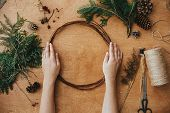 Making Christmas Wreath. Hands Holding Wooden Circle And Fir Branches, Pine Cones, Thread, Scissors, poster