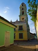 Old church sidelined by colorful houses in the colonial town of Trinidad in Cuba, a famous touristic landmark on the caribbean island poster