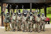 stock photo of paintball  - Boys dressed in camouflage stand in a row on a paintball base - JPG