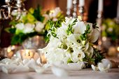 a white wedding bouquet on a dinner table during a reception. shallow depth of field