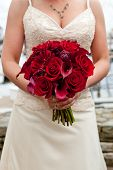 a bride holding her red wedding bouquet of flowers