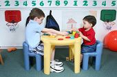 Boys Sharing Colorful Doah At Preschool