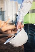 A Civil Engineer Holds A Helmet In His Hand At A Construction Site poster