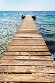 Wooden Pier On Coast Of Coral Beach