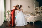 Gorgeous Bride In White Luxury Dress Is Getting Ready For Wedding.  Woman Putting On Dress. Stylish  poster
