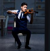 Young musician man practicing playing violin at home poster