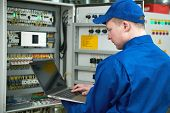 Electrician measures electrical paramenters with tester multimeter equipment at electrical fusebox o poster