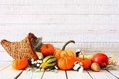 Thanksgiving Cornucopia Filled With Autumn Vegetables And Pumpkins Against A Rustic White Wood Backg poster