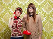 stock photo of dork  - funny nerd humor couple talking retro vintage red telephone on wallpaper - JPG