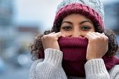 Closeup face of happy african girl holding woolen scarf with hands over nose to protect from the fro poster