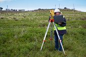 stock photo of theodolite  - Engineer with a theodolite for measuring topographic - JPG