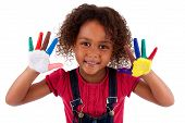 stock photo of biracial  - Little African Asian girl with hands painted in colorful paints - JPG