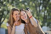 image of two women taking cell phone  - Photo of two girls smiling while taking photo with cell phone - JPG
