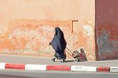 stock photo of yashmak  - Muslim woman is walking down the street - JPG