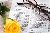foto of bible verses  - Holy Bible opened to the book of Psalms chapter 103 with a yellow rose and reading glasses - JPG