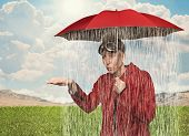 pic of ironic  - a girl caught in a rain shower under her umbrella - JPG