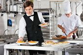 stock photo of trays  - Young waiter placing dishes in tray with chef working in commercial kitchen - JPG
