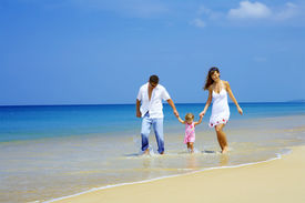 picture of beach holiday  - view of young family having fun on the beach - JPG