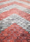 Abstract Background Texture Of Cobblestone Paving Road With Red And Gray Arrows