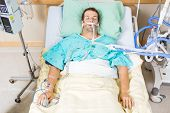 stock photo of intensive care  - High angle view of critical patient with endotracheal tube resting on bed in hospital - JPG