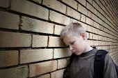 foto of sob  - upset boy leaning against a wall - JPG