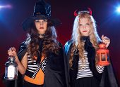stock photo of warlock  - Portrait of two Halloween girls with lanterns looking at camera - JPG