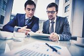 stock photo of meeting  - Image of two young businessmen discussing document in touchpad at meeting - JPG