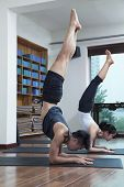 stock photo of bending over backwards  - Two people with legs raised doing yoga in yoga studio - JPG