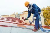 stock photo of industrial safety  - roofer builder worker with pulverizer spraying paint on metal sheet roof - JPG