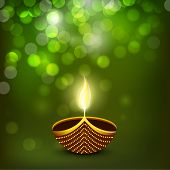 stock photo of lakshmi  - Indian festival of lights Happy Diwali greeting card or background with illuminated oil lit lamp on shiny green background - JPG