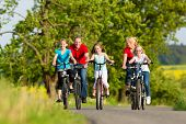 image of bike path  - Family with three girls having a weekend excursion on their bikes or bicycles on a summer day in beautiful landscape - JPG