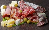 picture of smoked ham  - Arrangement of Delicatessen Cold Cuts with Smoked Ham Pepperoni Salami Finocchiona Green Olives Grana Padano and Camembert Cheese closeup on Dark Wooden background - JPG