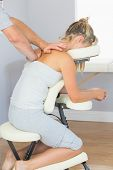 Masseur treating clients shoulder in massage chair in bright room