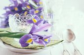 image of purple iris  - Festive table setting with purple iris flowers vintage cutlery and candles.