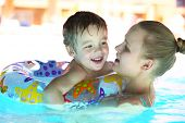 picture of rough-water  - Mother and her little son with floating ring swimming in rough water of the pool - JPG