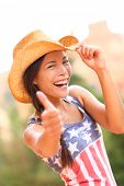 picture of cowgirl  - American cowgirl woman happy excited giving thumbs up wearing cowboy hat outdoors in countryside - JPG