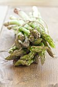 image of bundle  - Fresh asparagus in a bundle on woooden table - JPG