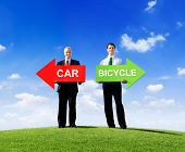 Two Businessmen Holding Arrows for Car and Bicycle