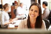 stock photo of pacific islander ethnicity  - Businesswoman Working At Desk With Meeting In Background - JPG