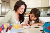 image of homework  - Mother Helping Daughter With Reading Homework At Table - JPG
