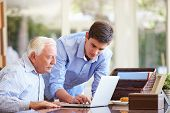 stock photo of 16 year old  - Teenage Grandson Helping Grandfather With Laptop - JPG