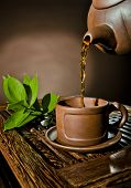picture of loam  - vertical photo of the clay teapot tea flow in cup on brown background tea ceremony - JPG