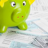 stock photo of cpa  - US Tax Form 1040 with green piggy bank and dollars - JPG