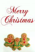 foto of cursive  - A Christmas Gingerbread cookie family of man woman and child is isolated on a white background with written cursive text Merry Christmas - JPG