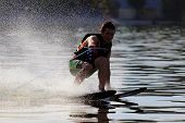 stock photo of watersports  - athlete touches the water when riding on water skis - JPG