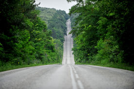 stock photo of long winding road  - Long and winding empty road through the forest - JPG